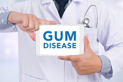 Man holding a sign with gum disease on it