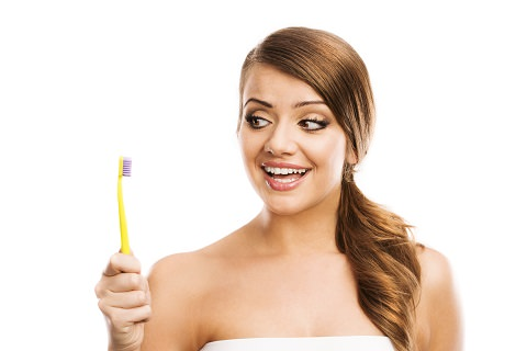 A woman looking at her toothbrush: Teeth Whitening review