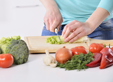 A person cutting up fresh vegetables