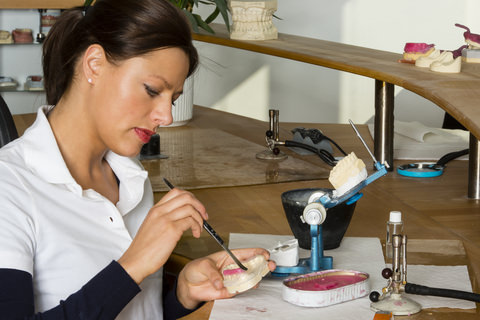 A dental technician working on dentures