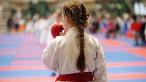 A girl using a mouthguard at a karate tournament