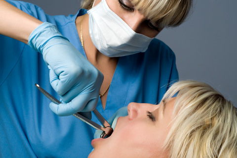 A dentist carefully extracting a lady's tooth