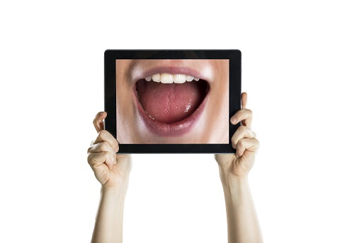 A lady looking at her smile using a tablet