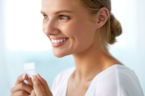 A lady using teeth whitening strips