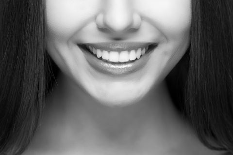 Black and white image of a woman smiling with white teeth