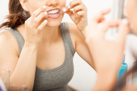 A woman putting on a teeth whitening strip