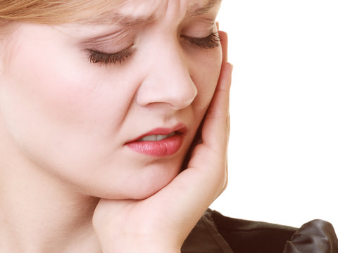 A lady in pain from wisdom teeth recovery