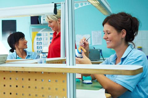 A dental technician working in a dental lab