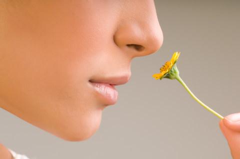 A lady smelling a flower