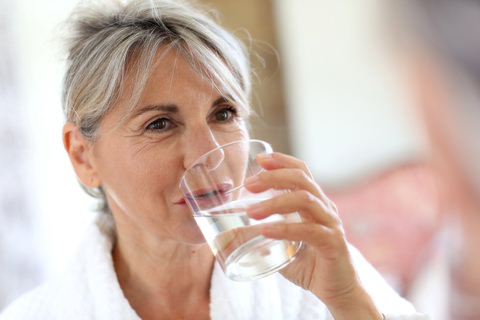 A woman using warm water to rinse her mouth