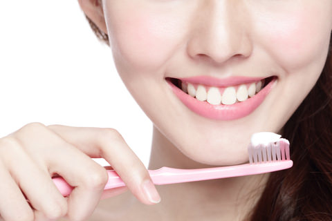 A lady brushing her teeth