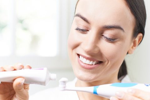 A lady applying toothpaste to a brush