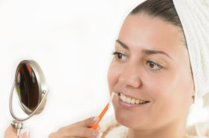 A lady using a interdental brush feature image