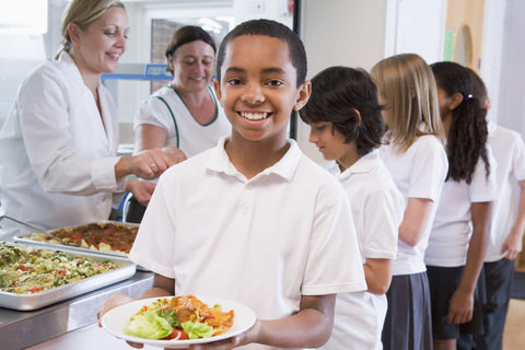 A boy with a plate of food at lunch time