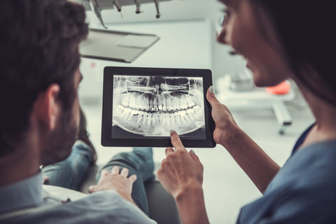 A dentist showing her patient an X-Ray of his teeth