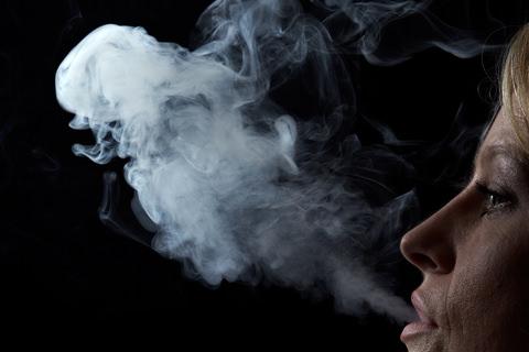 A lady exhaling smoke