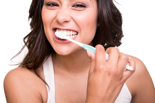 A lady brushing her teeth too hard