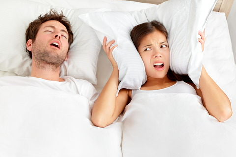A man snoring in bed with his partner