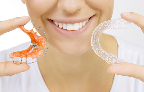 A lady holding up two forms of a retainer