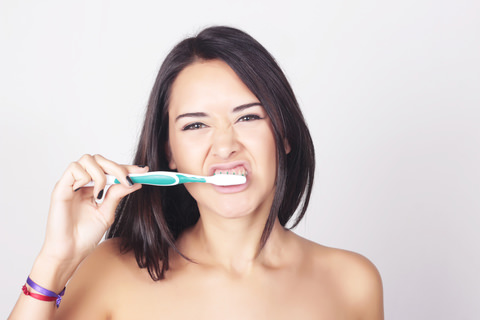 A lady brushing her teeth