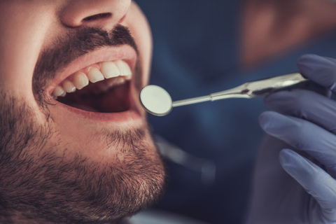 A man having his airway and mouth inspected by his dentist