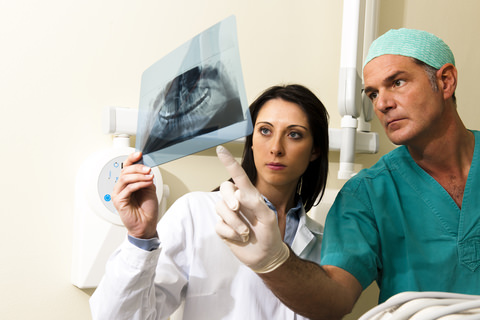 A specialist dentist looks at a X-ray