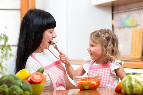 A child eating a healthy meal with her mum