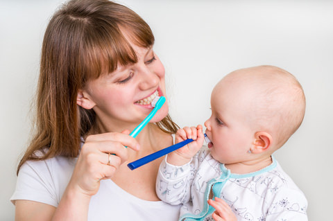A mum showing her child how to brush