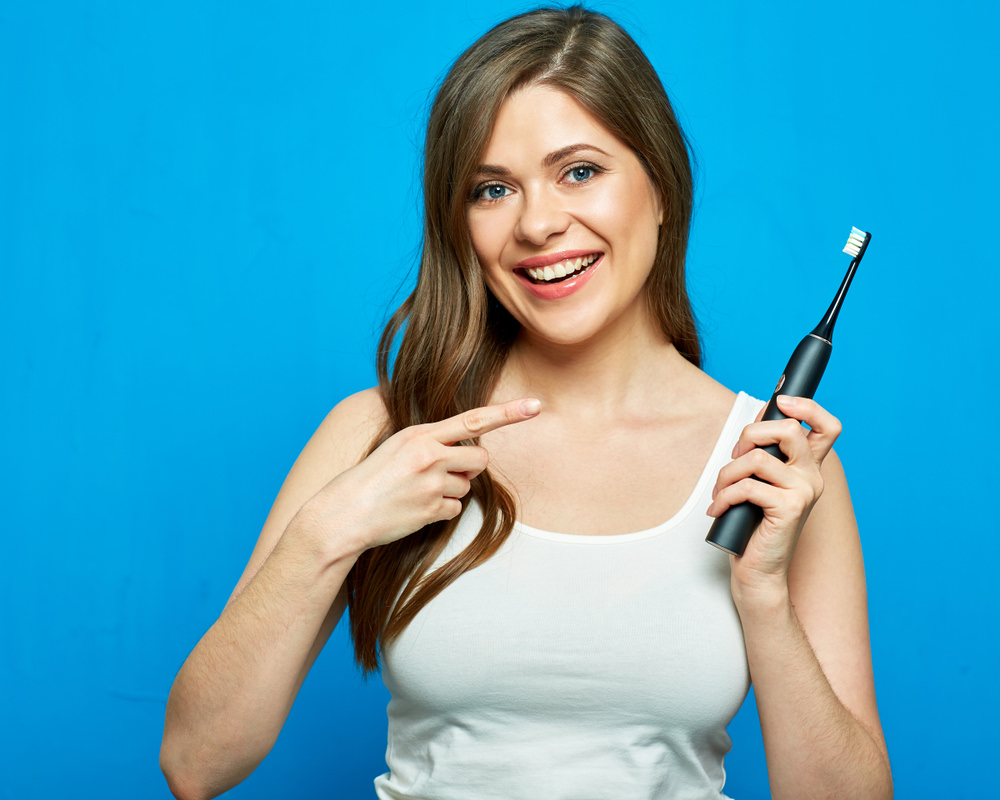 A lady with an electric toothbrush