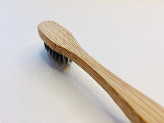 a side and back view of the colgate bamboo charcoal toothbrush
