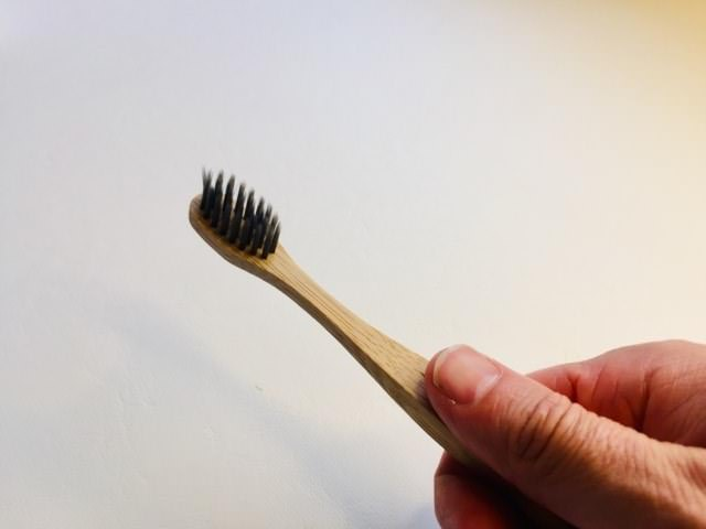 Holding the colgate bamboo charcoal toothbrush