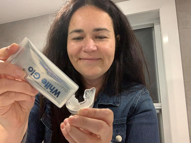 Renata apply White GLO's gel into her mouth tray