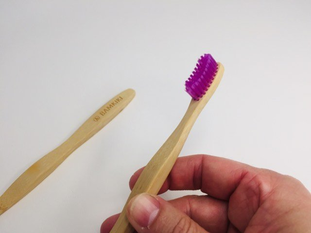 holding the handle of the bamkiki bamboo toothbrush