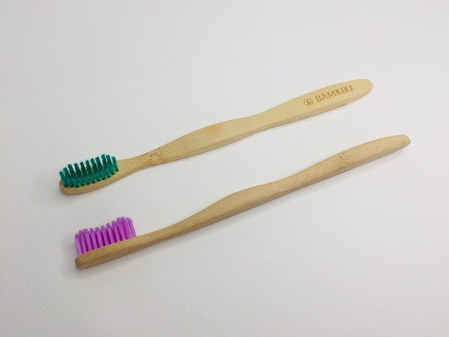 two bamkiki bamboo toothbrushes on a table