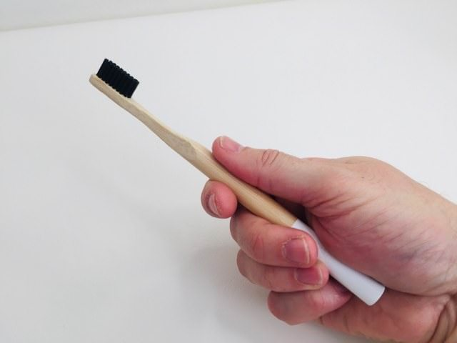 holding the kappi bamboo toothbrush in my hand