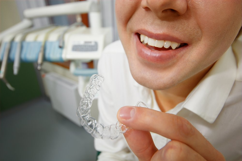 A dentist looking at a clear aligner