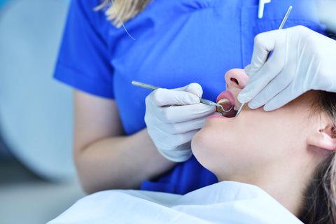 A person having their teeth cleaned by their dentist