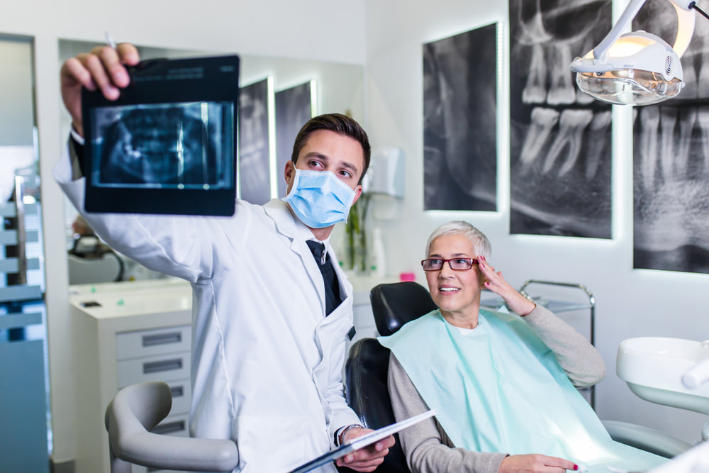 A dentist checking an X-Ray of a patient