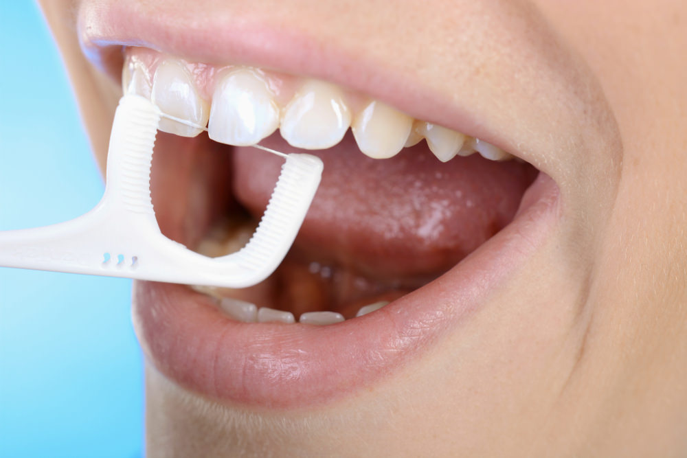 A person flossing as part of their dental hygiene routine