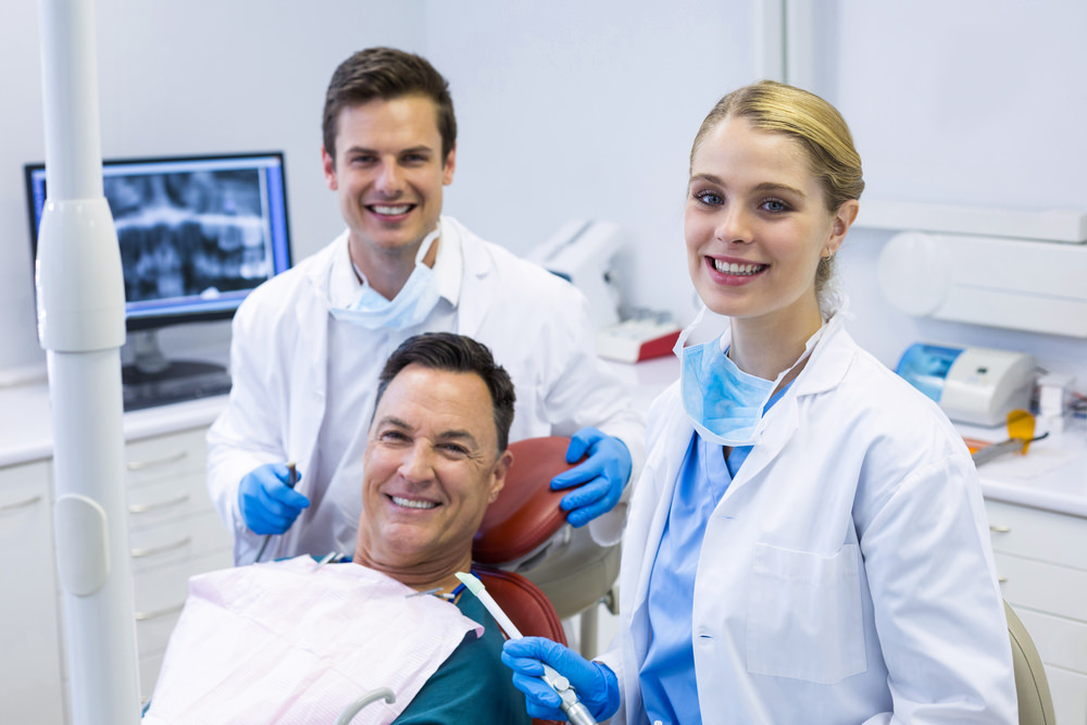 A dentist and Hygienist with their patient