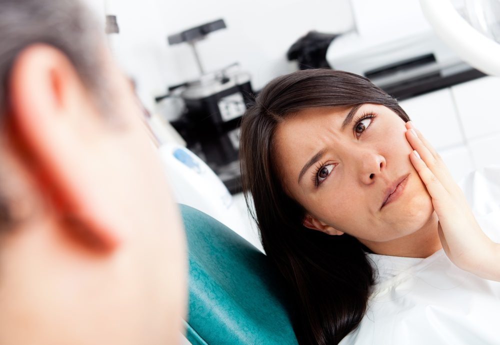 A woman in pain at the dentist Root Canal Treatment