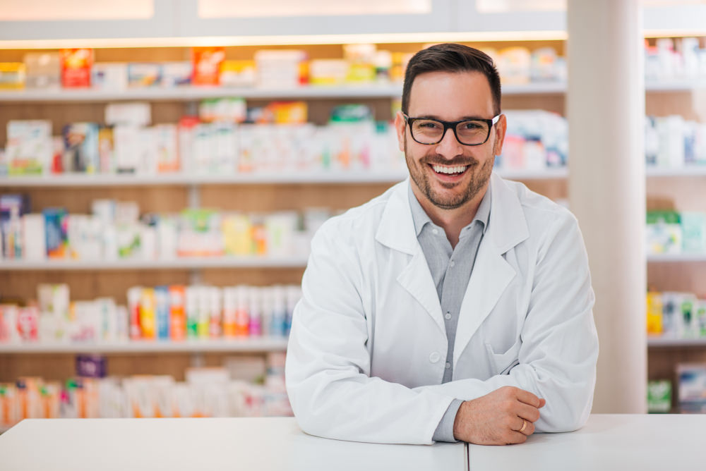 A male pharmacist with medication behind him
