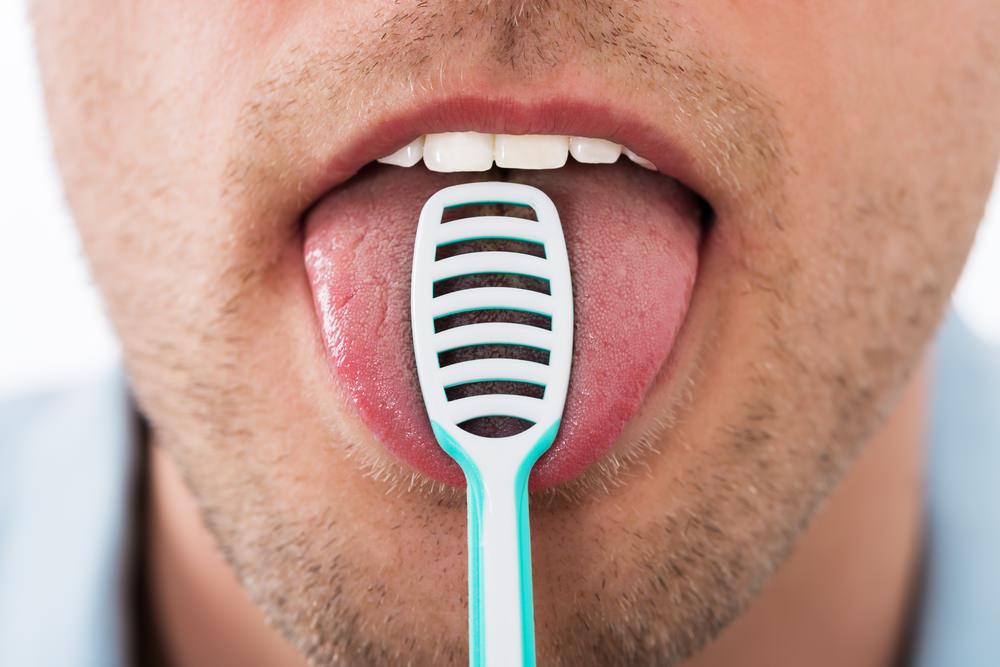 A man using a tongue scraper