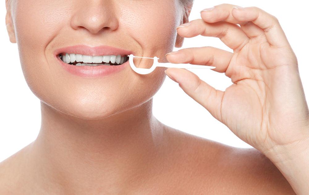 A lady using Dental floss picks