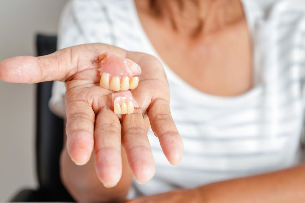 A lady holding partial dentures