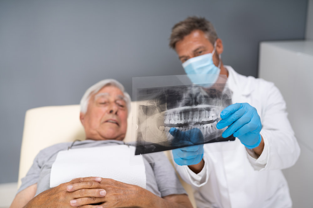 A patient looking at his x-ray with his dentist