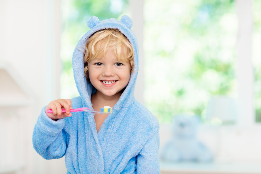 A young boy with a adult toothbrush