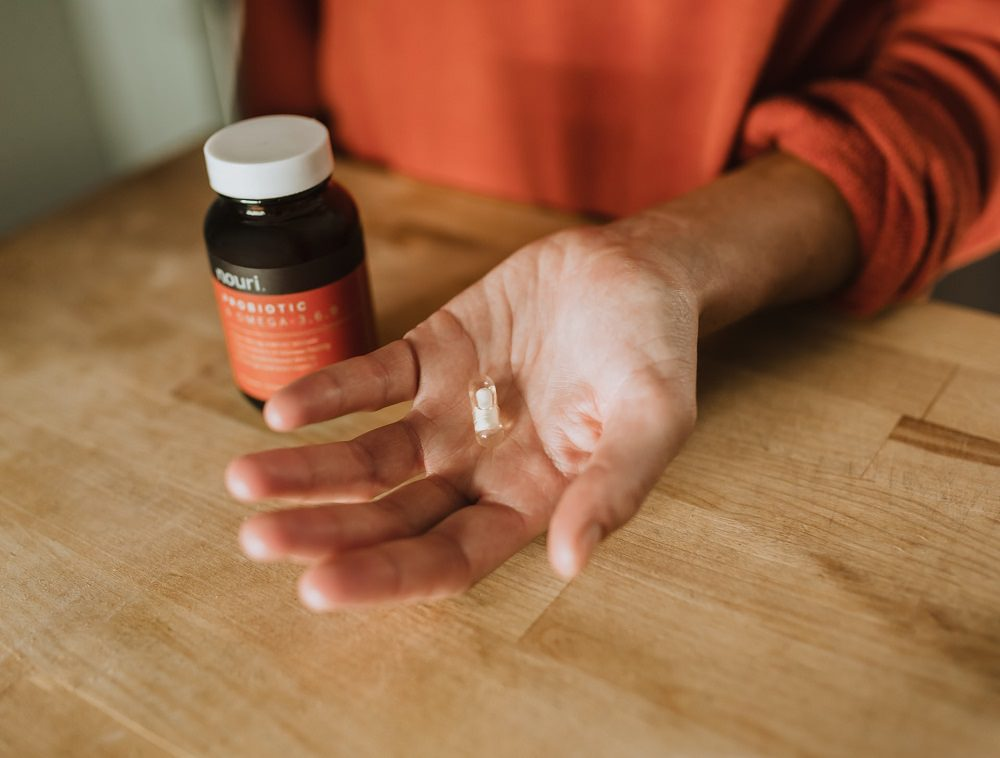 A lady holding a probiotic tablet